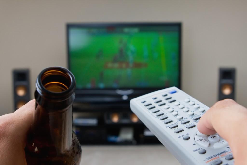en mand sidder og ser fjernsyn med en øl