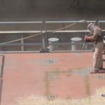 en sandblæser er i gang med en metaloverflade i sikkerhedsudstyr