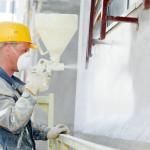 mand med gul sikkerhedshjem facademaler med hvid maling